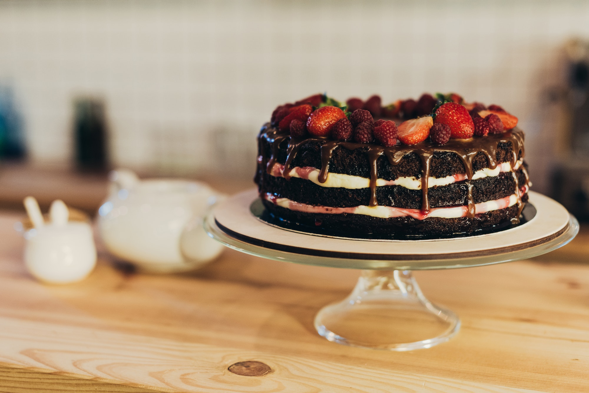 delicious chocolate cake with fruits on cake stand on a wooden table