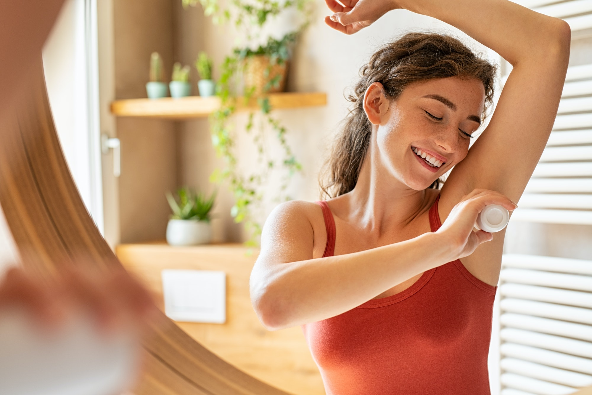 Happy young woman using roll on deodorant