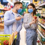 Young couple in masks shopping in supermarket